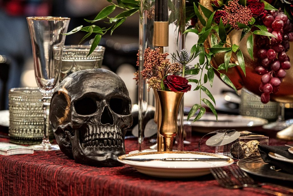 Table top with dark skull and flowers surrounding place setting.